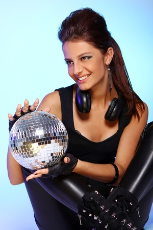 Beautiful girl with headphones and disco ball over light blue background photo