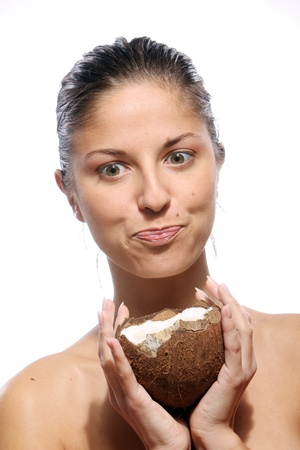 Beautiful woman with coconut in hands over white background photo