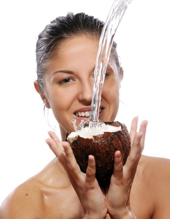 Beautiful woman with coconut in hands over white background
