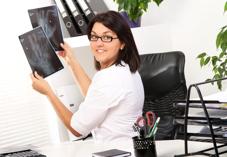 Young woman doctor is looking at xray of broken hand Stock Photo - 11209666