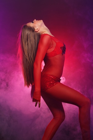Sexy dancer in red with smoke around photo