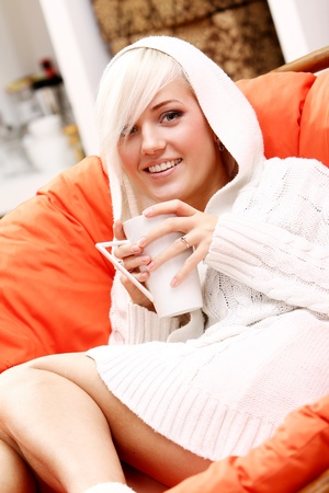 Beautiful girl relaxing at home with cup of hot drink photo