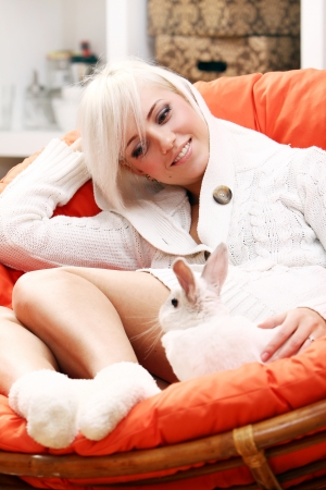 Young and cute blonde girl sitting in the chair with bunny photo