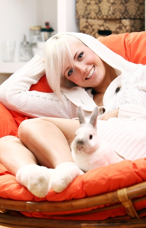 girl socks: Young and cute blonde girl sitting in the chair with bunny Stock Photo