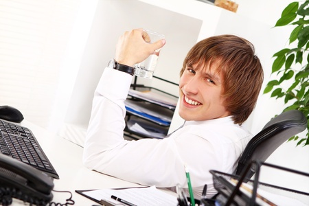 Young businessman with glass of water in his office photo