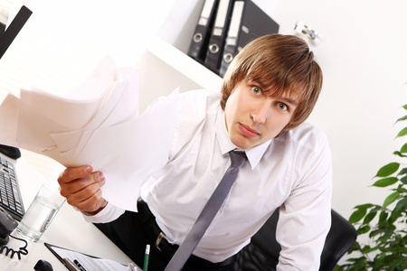 Angry businessman with documents in his office photo