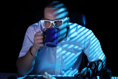 Funny nerd in glasses surfs internet at night time Stock Photo - 11929798