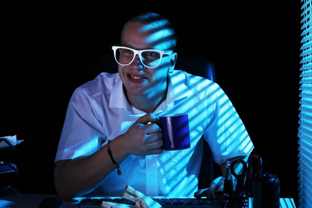 Funny nerd in glasses surfs internet at night time Stock Photo - 11929802