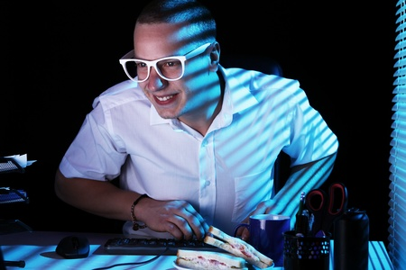 Funny nerd in glasses surfs internet at night time Stock Photo - 11929805