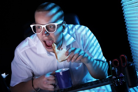 Funny nerd in glasses surfs internet at night time Stock Photo - 11929787