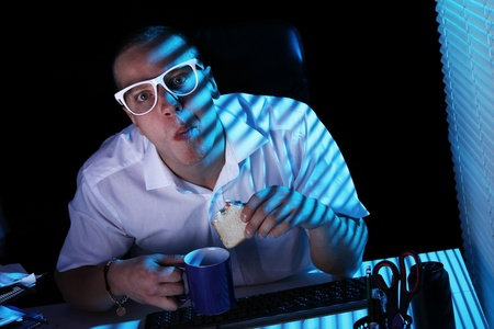 Funny nerd in glasses surfs internet at night time Stock Photo - 11929783
