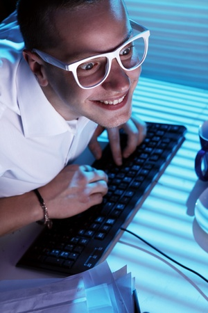 Funny nerd in glasses surfs internet at night time photo