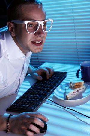 Funny nerd in glasses surfs internet at night time Stock Photo - 11929791