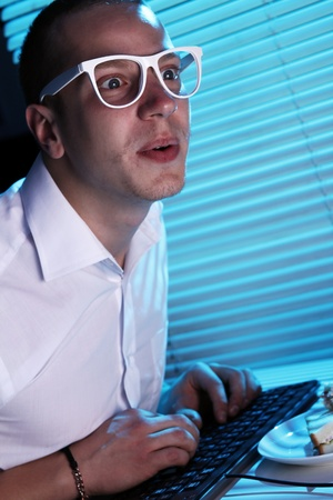 Funny nerd in glasses surfs internet at night time Stock Photo - 11929778