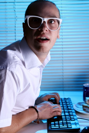 Funny nerd in glasses surfs internet at night time Stock Photo - 11929777