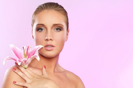 Young and beautiful woman with lily flower over pink background  photo