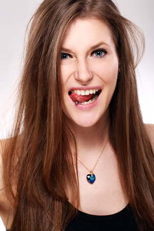 Young and beautiful girl with piercing in tongue photo
