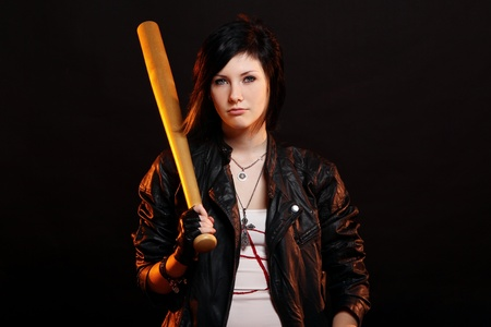 Young punk girl with baseball bat over black background photo