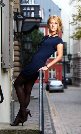Young and beautiful woman on the old city street photo