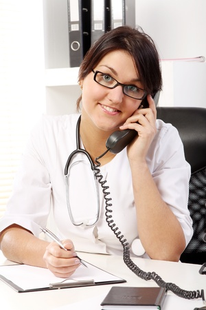 Young woman doctor talking by phone in her office  photo