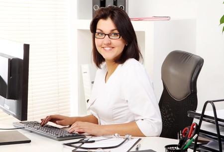 economia aziendale: Donna medico giovane e attraente nel suo ufficio