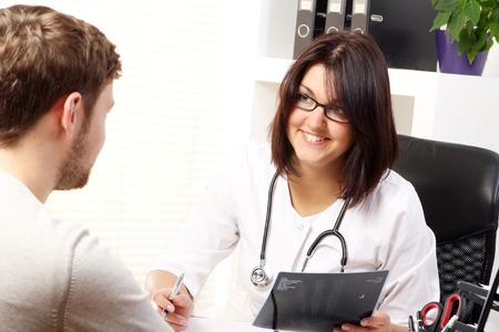 Woman doctor talking with patient in her office photo