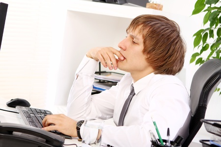 Young businessman thinking in his office  photo
