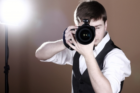 look at camera: Photographer with camera in studio