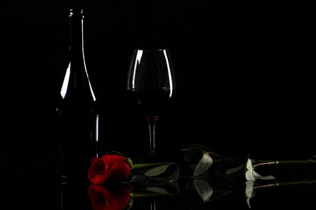 Red rose and wine in darkness photo