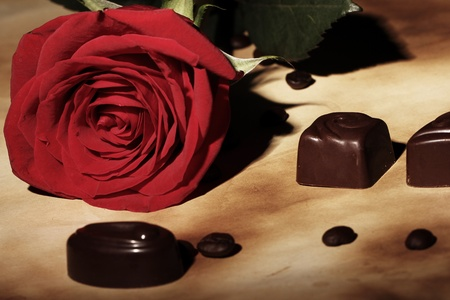 Close up of red rose and chocolate candies photo
