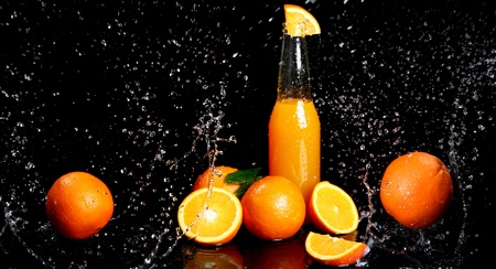 Fresh orange drink with splashes of water over black background photo