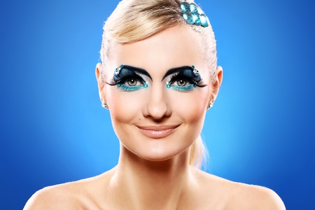 Beautiful blonde with artistic makeup over blue background Stock Photo - 12189502