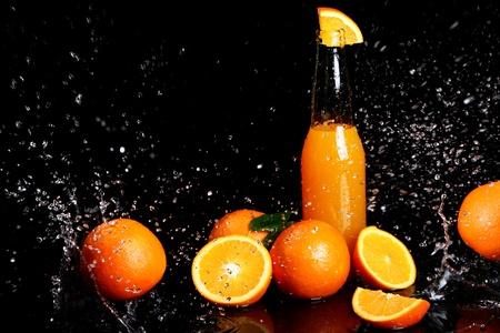 Fresh orange drink with splashes of water over black background photo