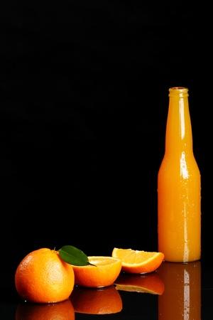Fresh orange drink over black background photo