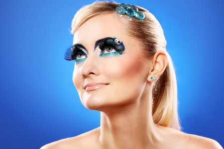 Beautiful blonde with artistic makeup over blue background Stock Photo - 12189487