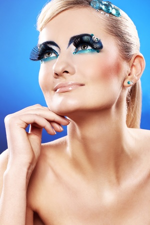 Beautiful blonde with artistic makeup over blue background photo