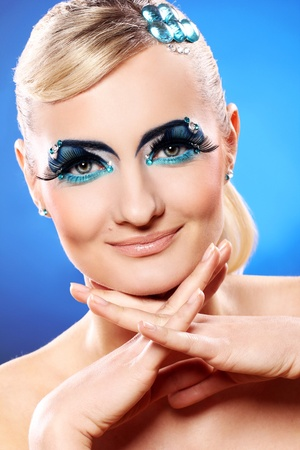 Beautiful blonde with artistic makeup over blue background Stock Photo - 12189742