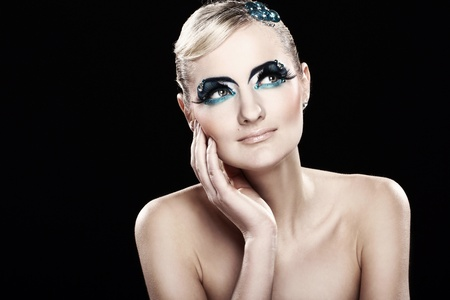 Beautiful blonde with artistic makeup over black background photo