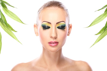 Beautiful blonde with artistic make- up and  bamboo leaves photo