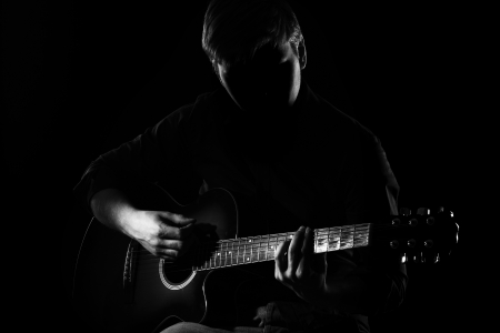 Man with guitar in the darkness