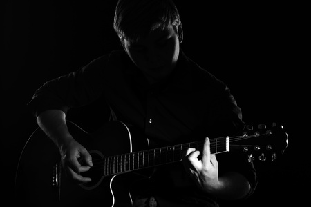 Man with guitar in the darkness photo