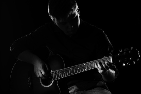 musician: Man with guitar in the darkness