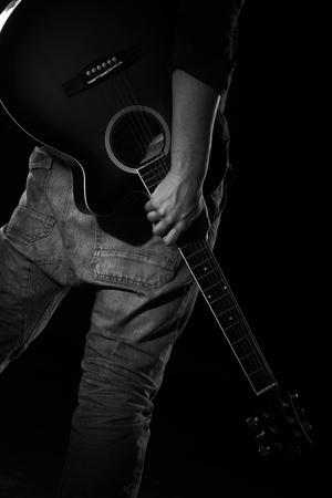 暗闇の中でギターを持つ男 写真素材