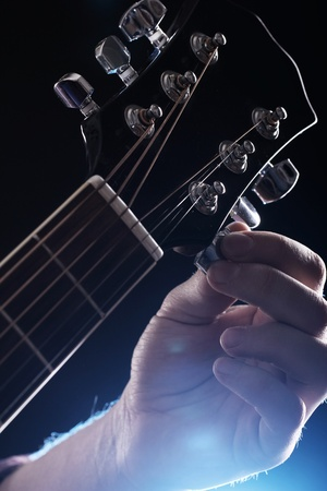 Musician playing on acoustic guitar photo
