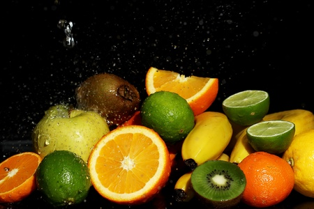 Fresh fruits and water splashes over black background photo