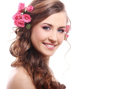 Beautiful woman with roses in hair over white background photo