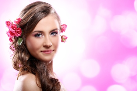 Beautiful woman with roses in hair over pink background photo