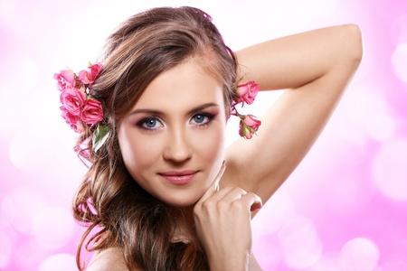 Beautiful woman with roses in hair over pink background Stock Photo - 12767676
