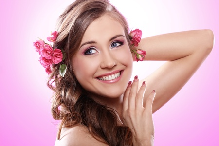 Beautiful woman with roses in hair over pink background Stock Photo - 12767674