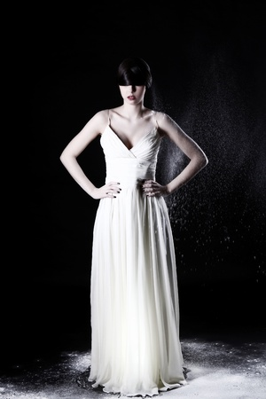 Beautiful girl in white dress and flying dust over black background Stock Photo - 12784087